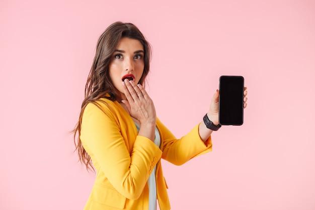 Mooie jonge vrouw die kleurrijke kleding draagt die zich geïsoleerd over roze bevindt, die leeg scherm mobiele telefoon toont