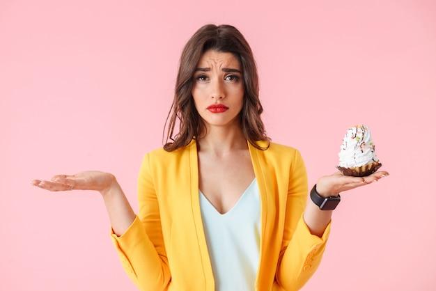 Mooie jonge vrouw die kleurrijke kleding draagt die zich geïsoleerd over roze bevindt, die romige cupcake houdt