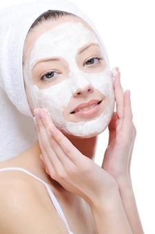 Mooie jonge vrouw die kosmetisch masker op haar gezicht op wit doet