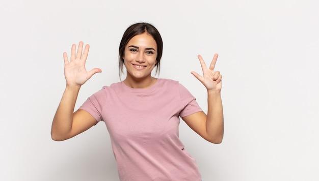 Mooie jonge vrouw die lacht en er vriendelijk uitziet, nummer acht of achtste toont met de hand naar voren, aftellend