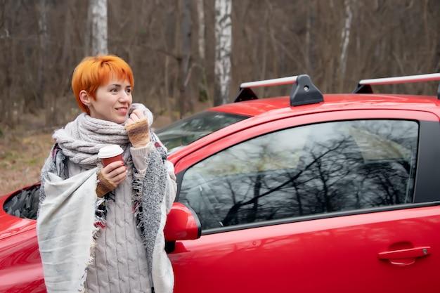Mooie jonge vrouw die lacht, koffie drinken uit een papieren beker naast de rode auto op de achtergrond van de herfst bos