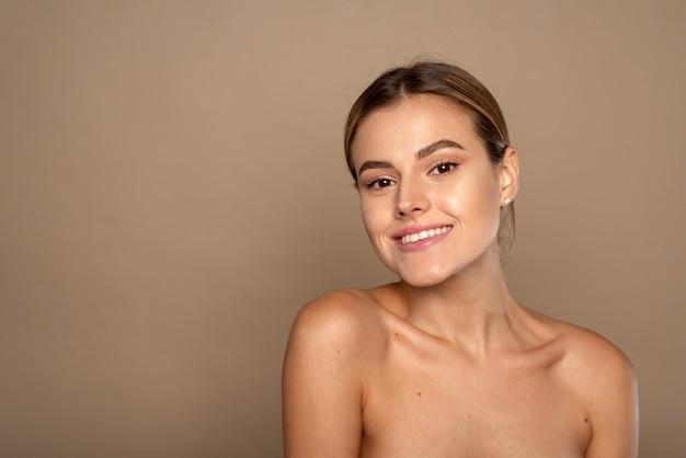 Mooie jonge vrouw die lacht na fantastische gezichtsbehandeling. gelukkig schoonheid dame opgewonden na spa-behandeling geïsoleerd op de achtergrond met kopie ruimte.