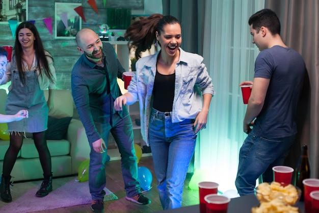 Mooie jonge vrouw die lacht tijdens het feesten met haar vrienden