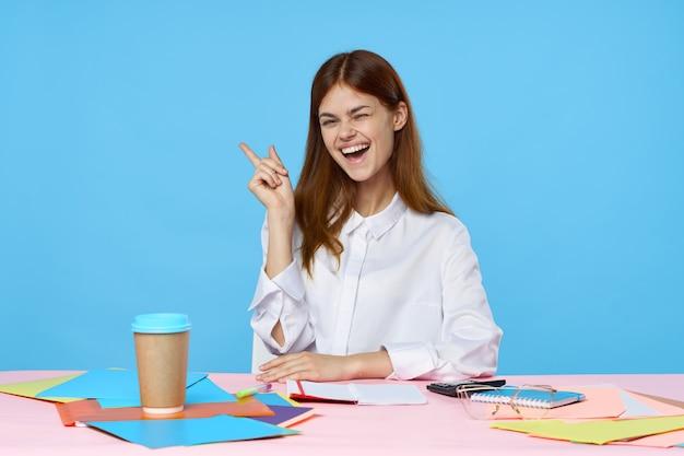 Mooie jonge vrouw die lacht zittend aan een creatieve tafel