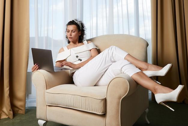 Mooie jonge vrouw die laptop gebruikt die in fauteuilconcept ontspannen zakendame in hotelruimte legt