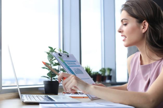 Mooie jonge vrouw die laptop gebruikt en ernaar kijkt terwijl ze op haar werkplek zit.