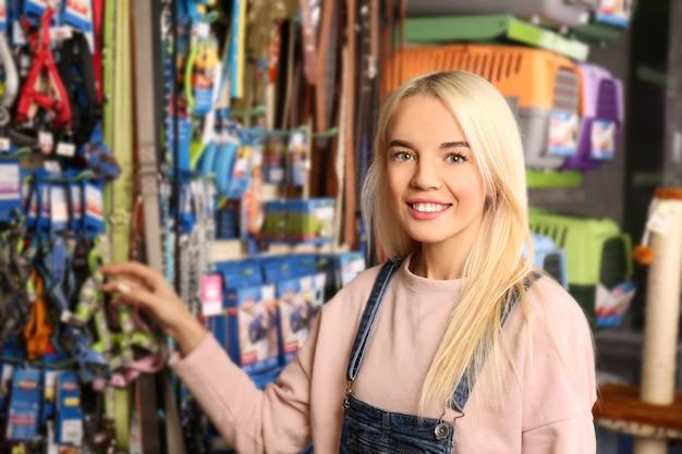 Mooie jonge vrouw die lood in dierenwinkel selecteert