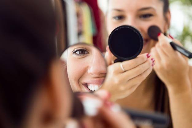 Mooie jonge vrouw die make-up dichtbij spiegel thuis maakt.