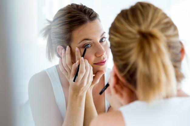 Mooie jonge vrouw die make-up doet dichtbij spiegel thuis.