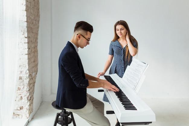 Mooie jonge vrouw die man het spelen piano bekijkt tegen muur