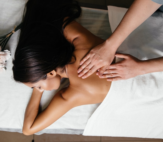 Mooie jonge vrouw die massage met stenen in kuuroordsalon heeft.