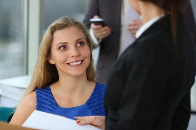 Mooie jonge vrouw die met collega's op het werk spreekt