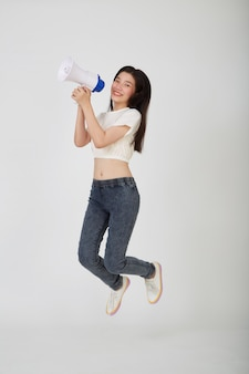 Mooie jonge vrouw die met een megafoon op witte studio springt