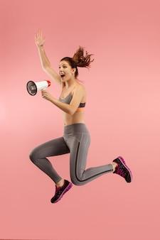 Mooie jonge vrouw die met geïsoleerde megafoon springt