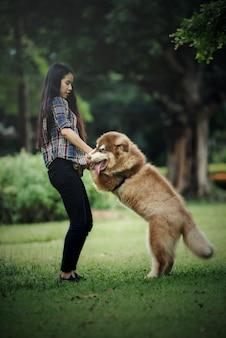 Mooie jonge vrouw die met haar kleine hond in een park in openlucht speelt. levensstijl portret.