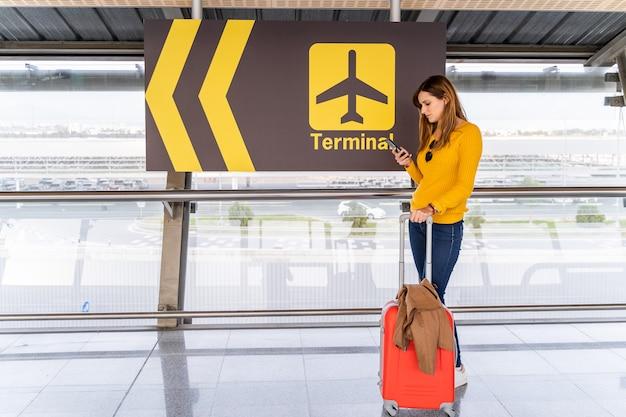 Mooie jonge vrouw die met haar mobiele telefoon en bagage op de luchthaven wacht