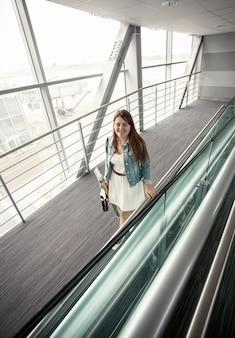 Mooie jonge vrouw die met handtas bij moderne luchthaventerminal loopt