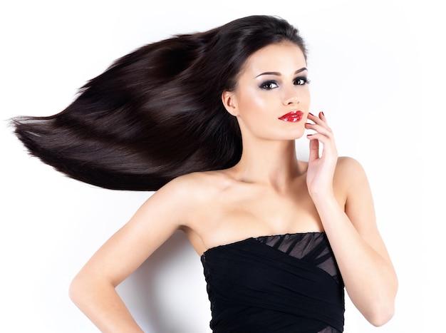 Mooie jonge vrouw die met lange bruine rechte haren camea bekijkt