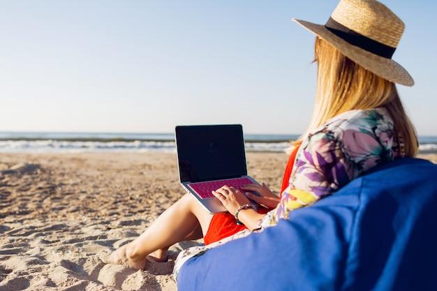 Mooie jonge vrouw die met laptop aan het tropische strand werkt