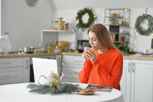 Mooie jonge vrouw die met laptop hete chocolademelk thuis op kerstavond drinkt