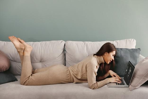 Mooie jonge vrouw die met laptop op bank nline shoping werkt