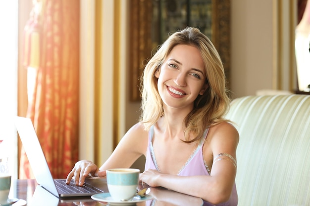 Mooie jonge vrouw die met laptop werkt en koffie in koffie drinkt