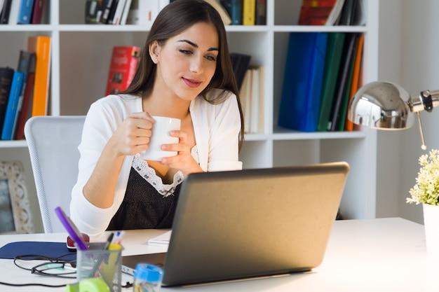Mooie jonge vrouw die met laptop werkt in haar kantoor.