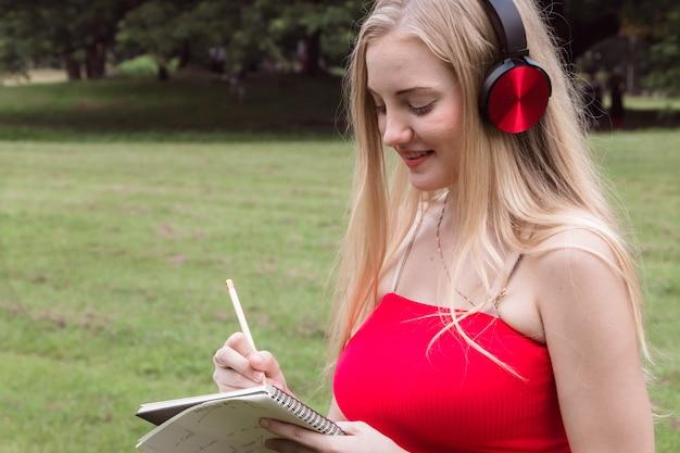 Mooie jonge vrouw die met nota schrijft bij park