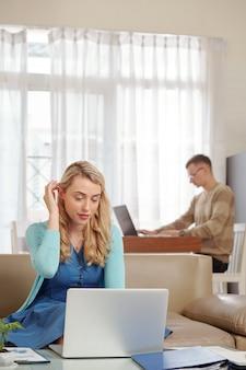 Mooie jonge vrouw die met papier en online document werkt wanneer haar echtgenoot aan keukentafel op achtergrond programmeert
