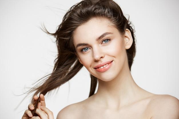 Mooie jonge vrouw die met perfecte schone huid wat betreft haar die over witte muur glimlachen glimlachen. gezichtsbehandeling.