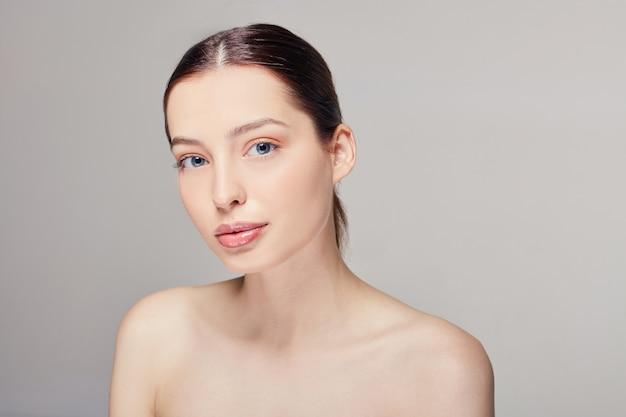 Mooie jonge vrouw die met schone huid recht kijkt.