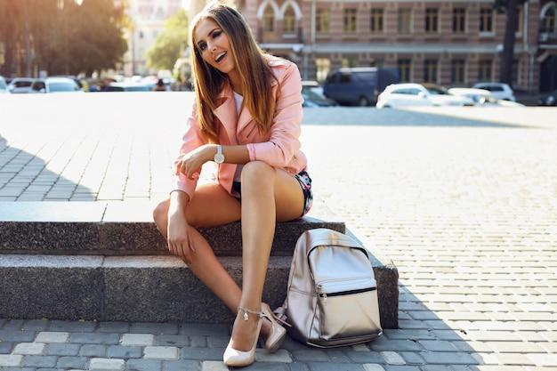 Mooie jonge vrouw die modieuze kleren, handtas, zilveren horlogeszonnebril dragen die in de stad gaan zitten. lichte make-up, bruin lichaam, lange benen