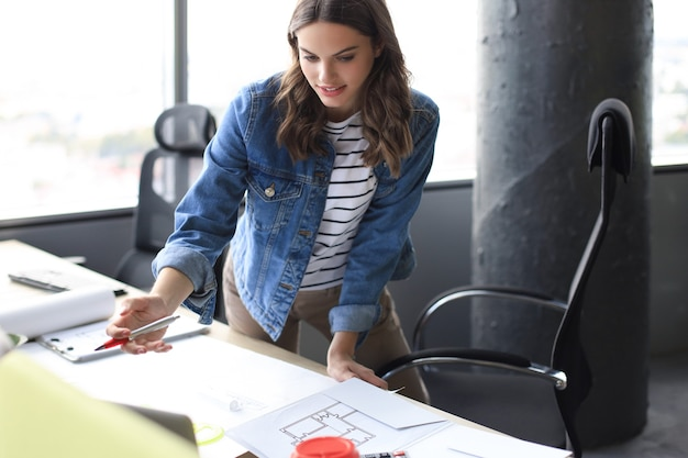 Mooie jonge vrouw die naar blauwdruk kijkt en glimlacht terwijl ze in het creatieve kantoor werkt.