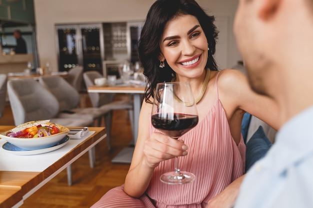 Mooie jonge vrouw die naar de man kijkt en glimlacht terwijl ze een glas wijn vasthoudt