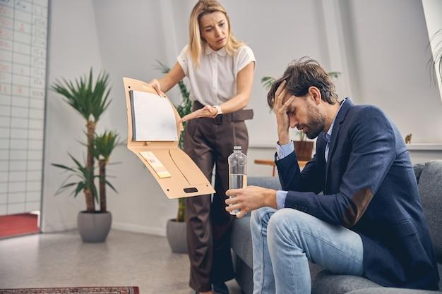 Mooie jonge vrouw die naar een mannelijke collega kijkt en naar documenten wijst terwijl de man migraine heeft