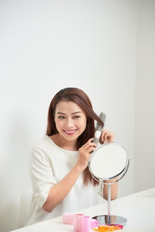 Mooie jonge vrouw die naar haar spiegelbeeld kijkt en haar lange haar borstelt