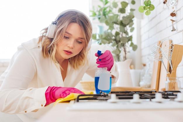 Mooie jonge vrouw die naar het gasfornuis kijkt terwijl ze het zorgvuldig schoonmaakt