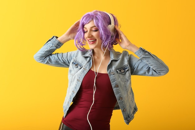 Mooie jonge vrouw die naar muziek luistert op geel