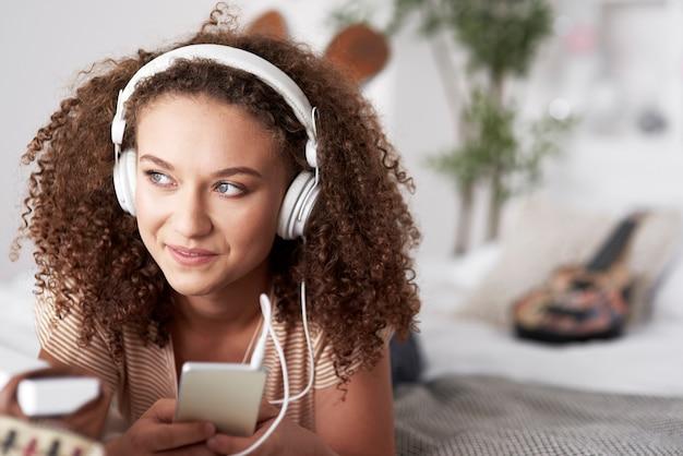 Mooie jonge vrouw die naar muziek luistert