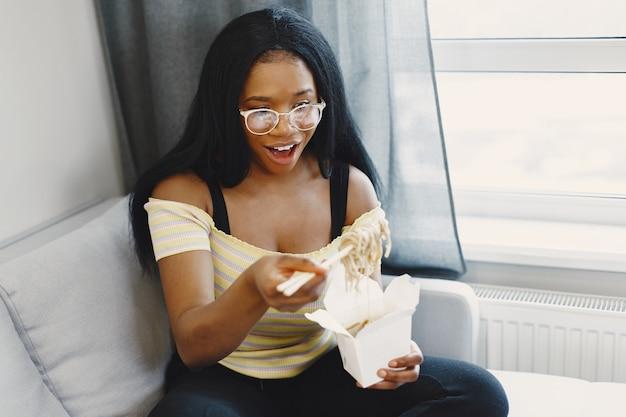 Mooie jonge vrouw die noedels eet