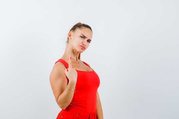 Mooie jonge vrouw die nummer één met vinger in rood mouwloos onderhemd toont en verward kijkt. vooraanzicht.