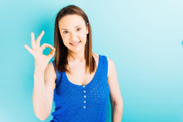Mooie jonge vrouw die ok of goedkeuringssymbool met hand met blauwe achtergrond en copyspace maakt