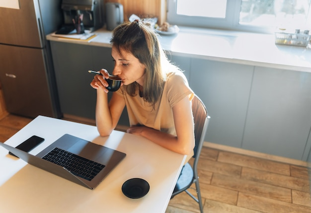 Mooie jonge vrouw die op afstand thuis werkt of studeert. freelance zittend in de keuken via internet met laptop
