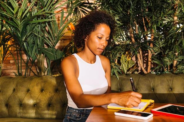 Mooie jonge vrouw die op agenda over de houten lijst schrijft