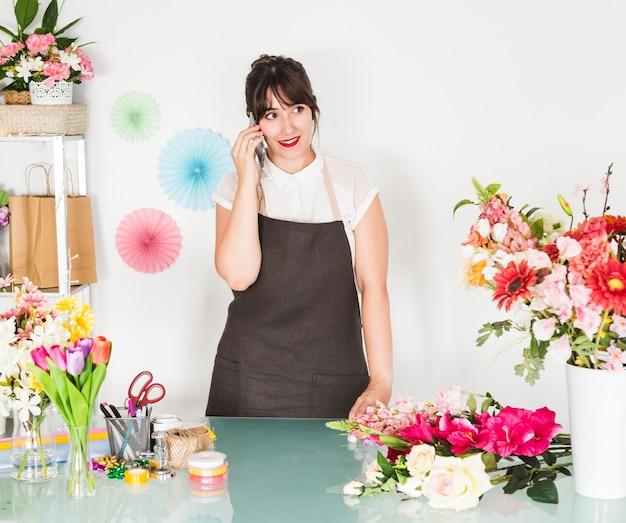 Mooie jonge vrouw die op cellphone met bloemen op bureau spreekt
