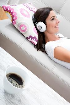 Mooie jonge vrouw die op de laag legt, die aan muziek luistert