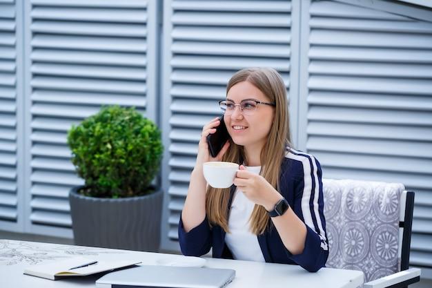 Mooie jonge vrouw die op een laptop werkt en aan de telefoon praat terwijl ze buiten in een café zit. jonge vrouw die laptop gebruikt voor werk. vrouwelijke freelancer die op een laptop op een terras werkt