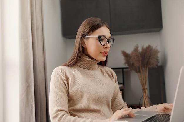 Mooie jonge vrouw die op een laptop werkt terwijl ze in de woonkamer koffie drinkt communiceert op internet werk op afstand e-learning concept