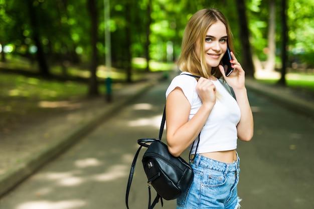 Mooie jonge vrouw die op een telefoon in het park van de stadszomer spreekt.