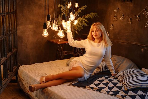 Mooie jonge vrouw die op het bed ligt dat heel wat gloeilampen feestelijk concept glanst